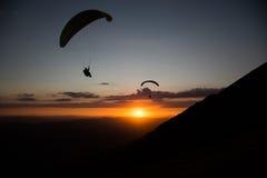 Parapentistes au coucher du soleil Photographie stock