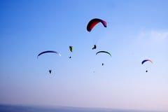 2 parapentistes dans le ciel, avec les canapies rouges et verts, ciel bleu Images stock