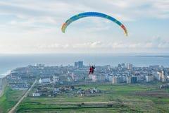 Parapentistes tandem volants au-dessus de la ville un jour ensoleillé Photographie stock libre de droits