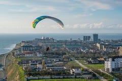 Parapentistes tandem volants au-dessus de la ville un jour ensoleillé Image libre de droits