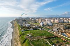 Parapentistes tandem volants au-dessus de la ville un jour ensoleillé Photos libres de droits