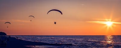 Parapentistes volant au coucher du soleil Photos stock
