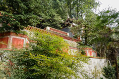 Parapets before ancient Chinese buildings on woody mountainside Royalty Free Stock Images