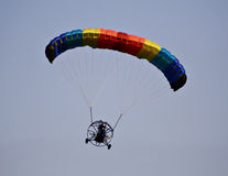 Paraplane in flight. A multi-colored parachute holds up this paraplane on a clear blue day stock images