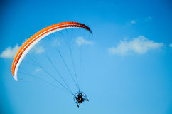 Paraplane. A multi-colored parachute holds  a paraplane on a clear blue day Royalty Free Stock Images