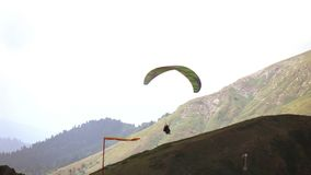 Paraplanner, starting with the mountain range. Tandem paragliders stock video