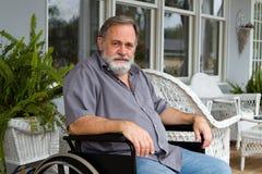 Paraplegic Man. Disabled paraplegic man sits depressed in his wheelchair posing on the porch Stock Photos