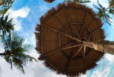 Paraplu die van palmbladen op tropisch strand wordt gemaakt Stock Afbeelding