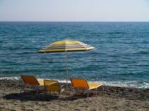 Paraplu en drie sunbeds op het strand Stock Fotografie