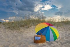 Paraplu en picknickmand tegen strand en wolken stock afbeelding