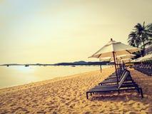 Paraplu en stoel op het tropische strandoverzees en oceaan bij sunris Stock Fotografie