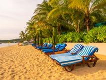 Paraplu en stoel op het tropische strandoverzees en oceaan bij sunris Stock Foto's