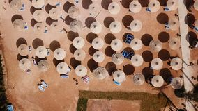 Paraplu's, ligstoelen en toeristen die op het strand ontspannen Lucht hoogste mening stock video