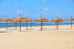 Paraplu's op zandig strand bij hotel in Marsa Alam - Egypte Stock Foto