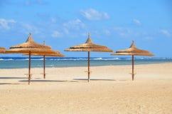 Paraplu's op zandig strand bij hotel in Marsa Alam - Egypte Stock Fotografie