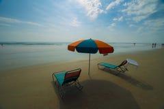 Paraplu in zand met stoelen Stock Afbeeldingen
