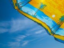Parapluie avec des palmiers contre le ciel bleu Image stock