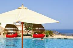 Parapluie blanc de lunettes de soleil sur le fond de la piscine avec des canapés de l'eau bleue et du soleil au paradis d'un bord photos libres de droits