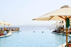 Parapluie blanc de lunettes de soleil sur le fond de la piscine d'infini avec des canapés de l'eau bleue et du soleil sur un bord image libre de droits