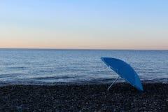 Parapluie bleu sur la plage La fin de la saison se baignante Photographie stock