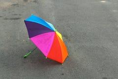 Parapluie d'arc-en-ciel se trouvant sur le trottoir après la pluie d'été, oubliée par un enfant Tristesse et solitude photos stock