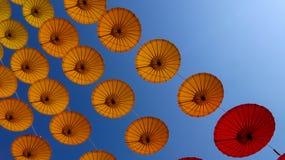 Parapluie de papier jaune et rouge accrochant sur la corde sur le fond de ciel Photographie stock libre de droits