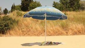 Parapluie de plage avec des serviettes sur une plage libre banque de vidéos