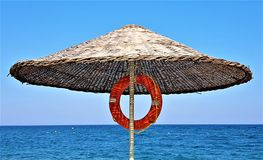 Parapluie de plage avec la bouée de sauvetage sur la côte de la mer Méditerranée, Kemer, Turquie images stock