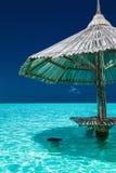 Parapluie de plage en bambou dans l'eau de l'île tropicale Image libre de droits