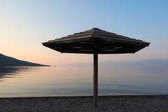 Parapluie de plage en bois à l'aube Images libres de droits