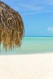 Parapluie de plage fait de feuilles de palmier sur la plage exotique Image stock