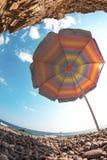Parapluie de plage sous les roches dessus autour de l'eau de mer Photo stock