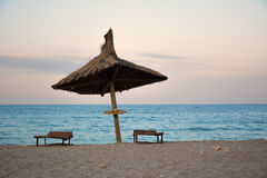 Parapluie de Reed sur la plage dans le coucher du soleil Image stock