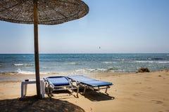 Parapluie en bois examinant la lumière du soleil et la chaleur Recliner réglable plié et dévoilé de plage faisant face à l'océan  photos libres de droits