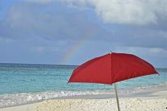 Parapluie et arc-en-ciel sur la plage Photographie stock libre de droits