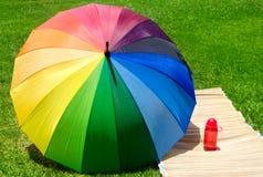 Parapluie et bouteille d'eau sur l'herbe Photos stock