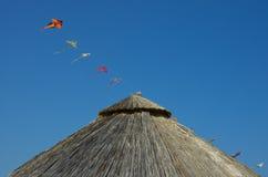 Parapluie et cerfs-volants de plage en bambou au-dessus d'un ciel bleu Image libre de droits