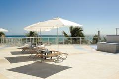 Parapluie et chaises latéraux de piscine photographie stock libre de droits