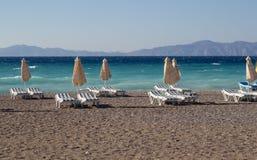 Parapluie et chaises longues rayés de plage Image stock