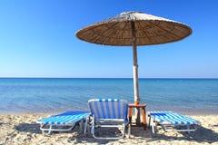 Parapluie et présidences de plage Photo stock
