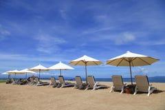 Parapluie et sièges multiples par la mer à l'arrière-plan de ciel bleu dans Bali Photographie stock
