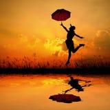 Parapluie heureux de prise de femme et sauter quand réflexion de l'eau de silhouette de coucher du soleil Copiez l'espace Photographie stock