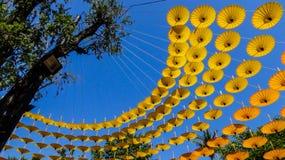 Parapluie jaune accrochant sur la corde, décoration dans le jardin à la fleur f Photographie stock libre de droits