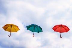 Parapluie jaune, parapluie vert et parapluie rouge flottant dans le ciel Images stock