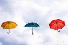 Parapluie jaune, parapluie vert et parapluie rouge flottant dans le ciel Image stock