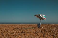 Parapluie laissé à une plage chaude photos libres de droits