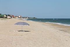 Parapluie rayé sur la plage Photos stock