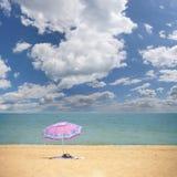Parapluie rose sur la plage tropicale Image stock