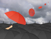 Parapluie rouge à disposition et entouré par un parapluie noir Image stock