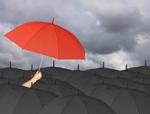 Parapluie rouge à disposition et entouré par un parapluie noir Photographie stock libre de droits